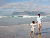 Father and son throwing stones in sea