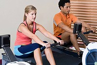 Woman and man on rowing machines