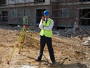 Engineer with theodolite and walkie talkie
