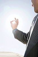 Man with fingers around sunlight