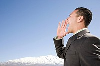 Businessman shouting by mountains