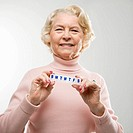 Caucasian senior woman holding pill box and smiling at viewer
