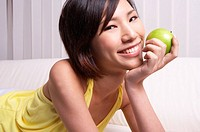 Portrait of Natural Young girl holding Apple, Smiling (thumbnail)
