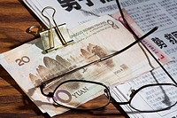 Eyeglasses and Chinese Yuan note on a newspaper