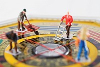 Figurines of manual workers working in feng shui compass