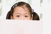 Close_up of a girl with a drawing paper