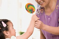 Close_up of a mature woman giving a candy to her granddaughter