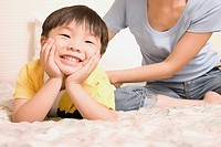 Close_up of a boy leaning on his elbows and her mother sitting near him