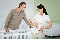 Parents standing in nursery, woman holding sleeping baby