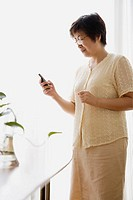 Side profile of a mature woman looking at a mobile phone