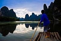 Side profile of a mature man rowing a wooden raft in a river, Li River, XingPing, Yangshuo, Guangxi Province, China