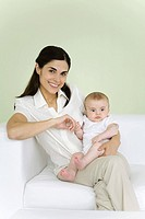 Woman holding baby on her lap, smiling at camera