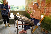 Senior man playing hammered dulcimer with his family standing beside him, Fuli Village, Yangshuo, Guangxi Province, China