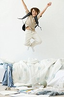 Boy jumping on bed in messy room, arms raised