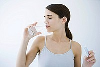 Woman drinking effervescent water, holding medicine packet (thumbnail)