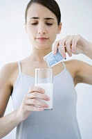 Woman pouring effervescent medicine into glass of water