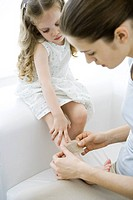 Mother putting adhesive bandage on young daughter's leg
