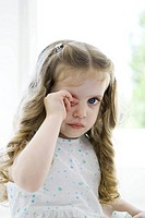 Little girl rubbing her eye, looking at camera (thumbnail)