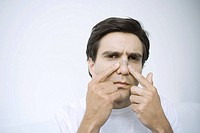 Man applying adhesive bandage on his nose, looking at camera