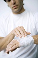 Man wrapping gauze around his wrist and hand, cropped view