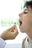 Child accepting pill with open mouth, cropped view