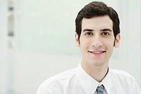 Young businessman smiling at camera, portrait (thumbnail)