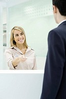 Professional woman standing behind counter, handing document to businessman