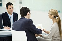 Professional meeting with clients, couple analyzing document together