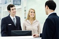 Customer service representatives smiling at businessman waiting at counter