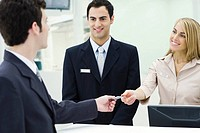 Man giving credit card to smiling customer service representatives