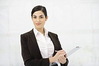 Businesswoman holding clipboard, taking notes, smiling at camera, portrait