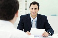 Businessman holding document, smiling at client