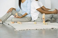 Couple sitting on the ground with building blocks, cropped view