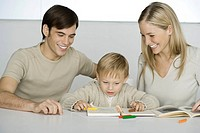 Little boy sitting at table with parents, coloring with crayons