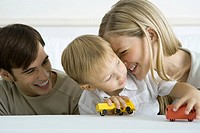 Little boy sitting with parents, playing with toy trucks, mother nuzzling his cheek