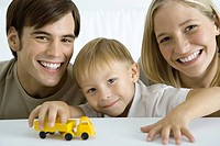 Family smiling at camera, boy playing with toy truck