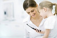 Mother and young daughter looking at cell phone together