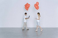 Young man and woman walking toward each other, both carrying laptop computers and heart balloons