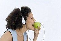 Woman wearing headphones plugged into apple, biting into apple, profile (thumbnail)