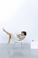 Young woman lounging in chair, listening to headphones connected to apple (thumbnail)