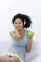 Woman listening to headphones connected to apple, eyes closed
