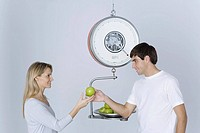 Man weighing apples on scale, giving woman one apple