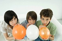 Mother and two sons inflating balloons, looking at camera, high angle view
