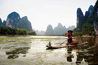 Fisherman on a bamboo raft with a hill range in the background, Guilin Hills, XingPing, Yangshuo (thumbnail)
