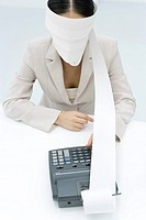 Businesswoman using adding machine, blindfolded with paper printout