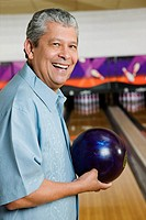 Hispanic man holding bowling ball