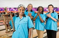 African woman holding bowling trophy while team applauds