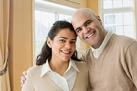 Hispanic couple smiling in livingroom