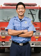 Asian firefighter next to fire truck (thumbnail)