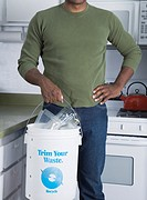 Mixed race man holding recycling bucket in kitchen